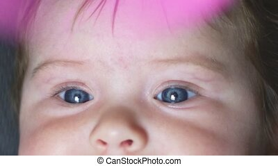 Super close-up shot in slow motion of a beautiful baby girl with blue eyes and a moving fan right on top
