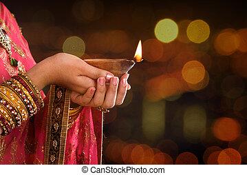 Close up Indian woman hands holding diya light - Close up...