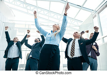 jubilant business woman standing in front of her colleagues