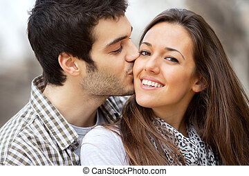 Close up portrait of boy kissing girlfriend on cheek outdoors.