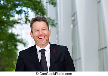 Close up laughing businessman standing outside in suit and tie