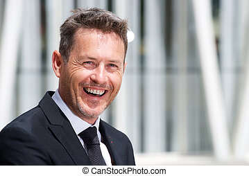 Close up laughing older businessman in suit and tie