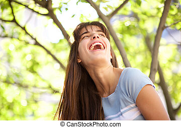 Close up laughing young woman in park
