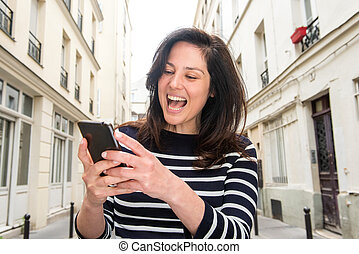 Close up laughing young woman looking at mobile phone in city