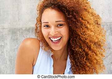Close up laughing young woman with curly hair