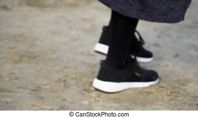 Close up legs in stylish sneakers walking on sand, slow...