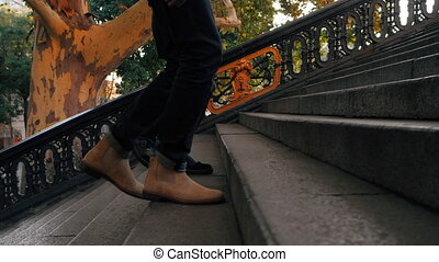 Close up legs of man and woman walking up on stairway. Feet...