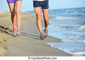 close up legs of young couple man and woman running in the sand on the shore of a beach by the sea during sunny summer holiday vacation