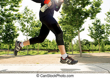 close up legs of young man running in city park with trees on summer training session practicing sport healthy lifestyle concept