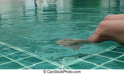 Close-up legs of young woman relaxing in hotel pool