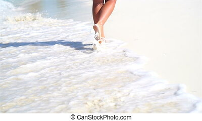 Close-up legs running along the white beach in shallow water. Concept of beach vacation and barefoot. SLOW MOTION.