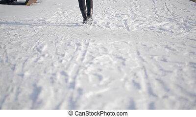 Close-up legs walking in street outdoors in snowy Russian winter