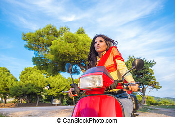 Close up lifestyle image of young fashionable woman in casual outfit sitting on scooter on the street.