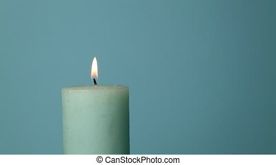 Close up light blue candle trembling flame