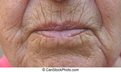 Close up lips of mature grandmother. Mouth of elder grandma sends air kiss into camera. Senior woman with wrinkled skin does kissing gesture. Slow motion.