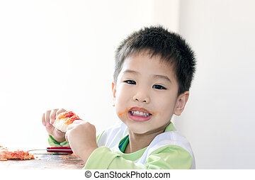 Close up little Asian boy eats pizza on white background