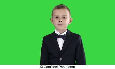 Little boy in a costume with a bow tie walking on a Green Screen, Chroma Key.
