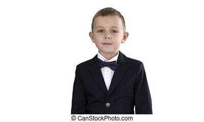 Little boy in a costume with a bow tie walking on white background.