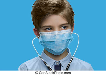 Close up little boy wearing medical mask.