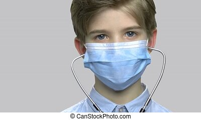 Close up little boy with medical mask and stethoscope.