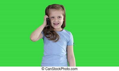 Little cute girl making a phone call while walking on a Green Screen, Chroma Key.