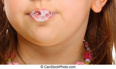 Close up little girl doing fun saliva bubbles - Close up...