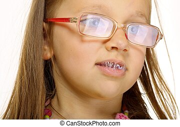 Close up little girl in glasses doing fun saliva bubbles