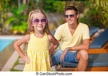 Close up little girl with her young dad at the swimming pool