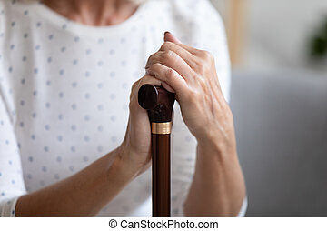 Close up lonely older woman holding hands on walking stick