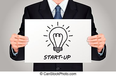 businessman holding start-up poster