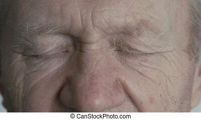Close up look at camera of old wrinkled handsome man