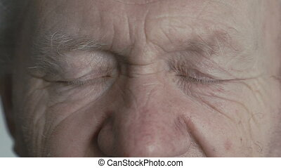 Close up look at camera of old wrinkled man