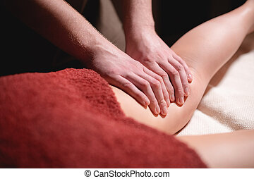 Close-up low key on woman's thigh massage in a professional premium spa salon, man masseur does in a dark room