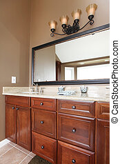 Close up luxury wood bathroom cabinets and mirror.