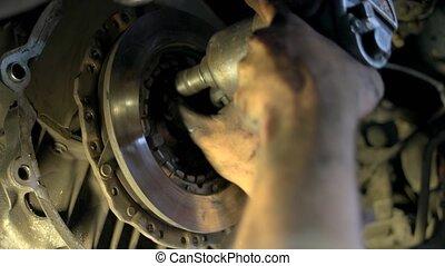 Close up machanic unscrewing bolts of a car clutch. ...