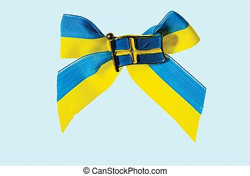 Close up macro view of metal badge in form of swedish flag on blue yellow bow isolate in blue background.