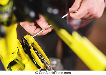Close-up maintenance of a mountain bike. Male hands adjust the chain tension. Technical condition monitoring in the workshop