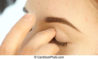 Close-up make-up artist hand, applying eyeshadow to woman's...