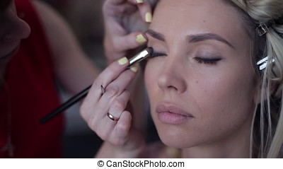 Close-up. Makeup artist stylist makes an image for a girl in a beauty salon