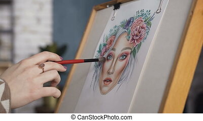 Close-up makeup of women's hands, which draws a sketch of the facial diagram. The girl artist paints a sketch on the face of the charts. Young woman in a bright studio draws a face chart using cosmetics for makeup