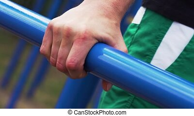 Close-up - Male Athlete Working Out on Bars