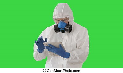 Male doctor in protective suit using digital tablet on a Green Screen, Chroma Key.