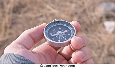 Close-up male hand holds a magnetic compass on a background ...