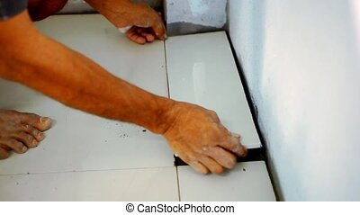 Close up male hands laying ceramic floor tiles.