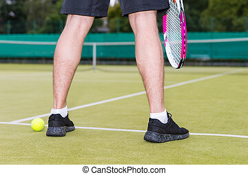 Close up male player's legs during the game on green grass court outdoors