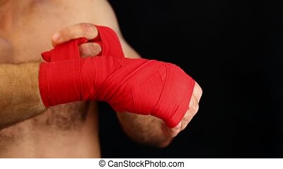 Close up man boxer wrapping red hand wraps over wrists preparing for fight, over black background with copy space, low angle view