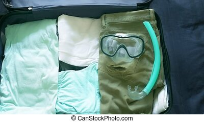close-up. man collects a suitcase on a trip to tropical countries with diving equipment in the sea