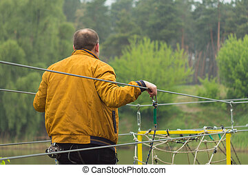 Close up man crossing the river on the rope bridge