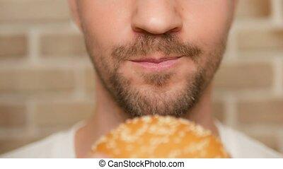 close up. man eating hamburger.