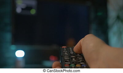 Close up man hand holding the TV remote control and changing...